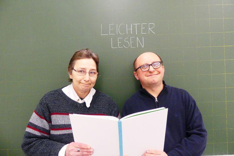 Monika Birk und Robert Gubitz stehen lächelnd vor einer grünen Schultafel. Darauf steht: Leichter lesen. Die beiden halten ein aufgeschlagenes Buch.