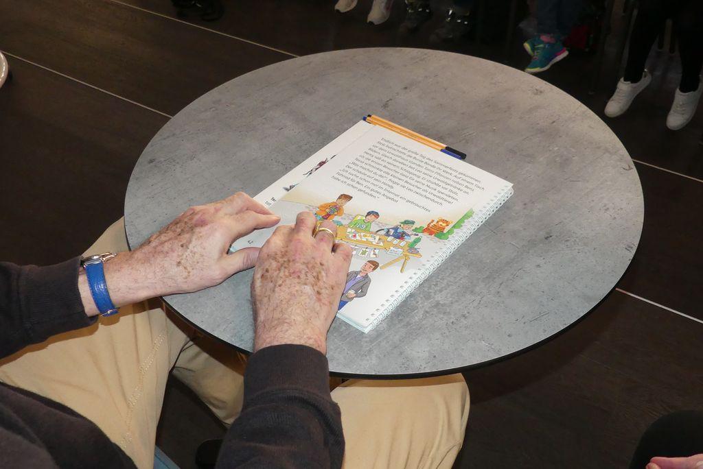 Peter Weiß ist blind und liest mit seinen Fingerspitzen ein Buch in Brailleschrift.