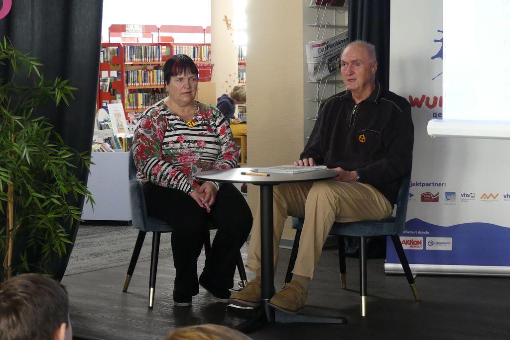 Anette und Peter Weiß erzälen beim Lesefest darüber, wie sie als blinde Menschen Bücher lesen. Die beiden sitzen an einem Tisch auf der Vorlesebühne.