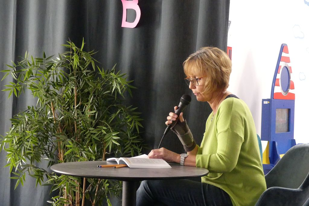Hildegard Legat sitzt mit einem Mikrofon an einem kleinen Tisch und liest ein Märchen in Leichter Sprache vor.