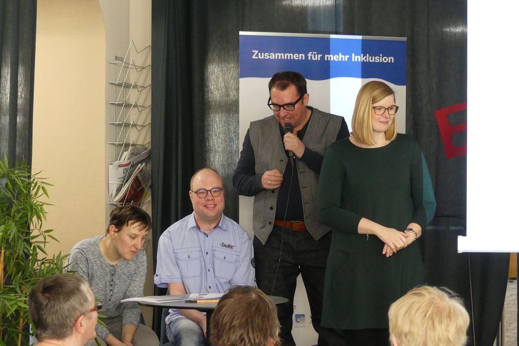 Von links: Am Tisch sitzen Maria Popp und Oliver Kuhn von der Prüfergruppe Alles klar. Volker Glombitza leitet die Prüfergruppe und erzählt gerade von der gemeinsamen Arbeit. Rechts steht die Gebärdensprachdolmetcherin Kathleen Entrich.