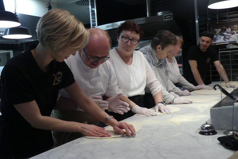 Unser Team lernt, Pizza sanft auszuformen mit den Händen.
