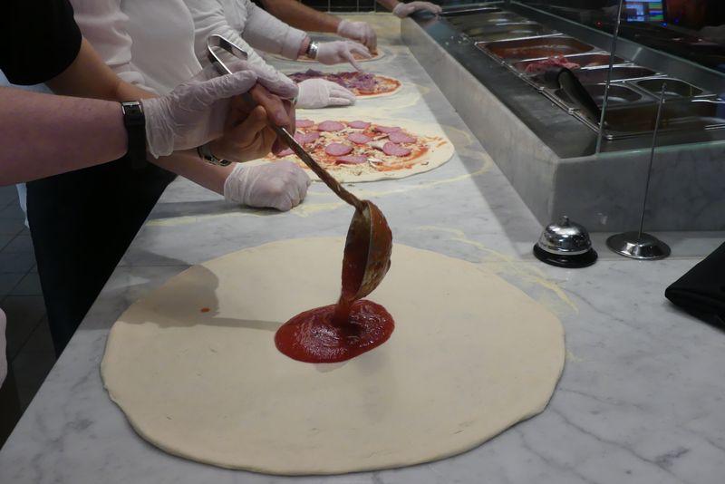 An der Marmoteheke sind Pizzaböden in verschiedenen Bearbeitungsstufen: Manche sind schon fertig belegt. Die vordere Pizza wird gerade mit einer Schöpfkelle Tomatensoße begossen.