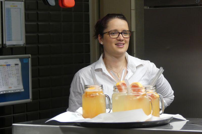 Julia steht hinter einem Tablett mit leckeren hausgemachten Limonaden.