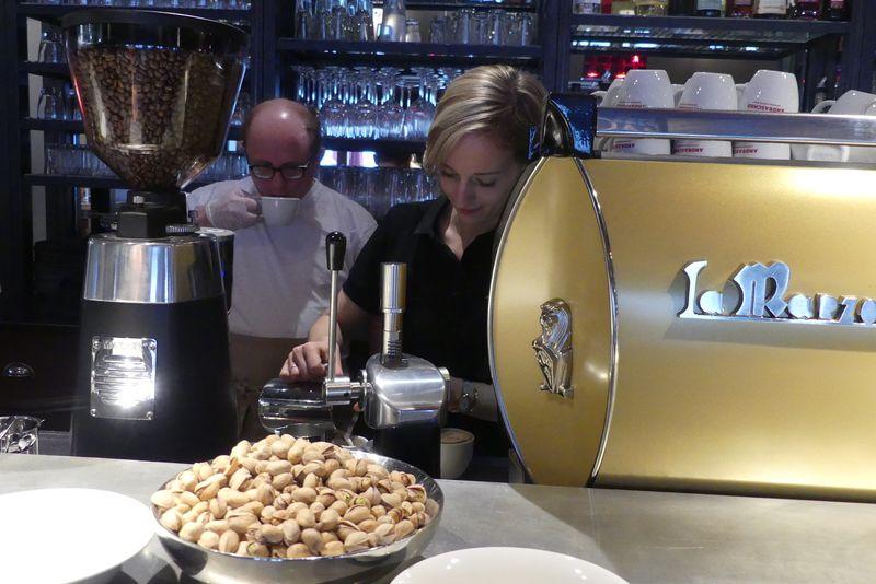 Isabell zeigt Roland, wie der Kaffeeautomat arbeitet. Roland trinkt genießerisch eine frischgebrühte Tasse.