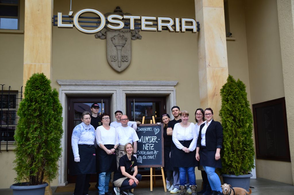 Gruppenfoto mit unseren Wundernetz-Kollegen und dem netten Team der L'Osteria vor dem Eingang des Restaurants in Amberg.