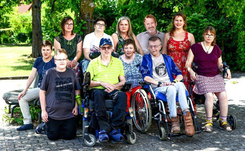 Gruppenbild mit allen Teilnehmer/innen beim Fotoshooting auf einer Bank unter einem Baum im hellen Sonnenlicht