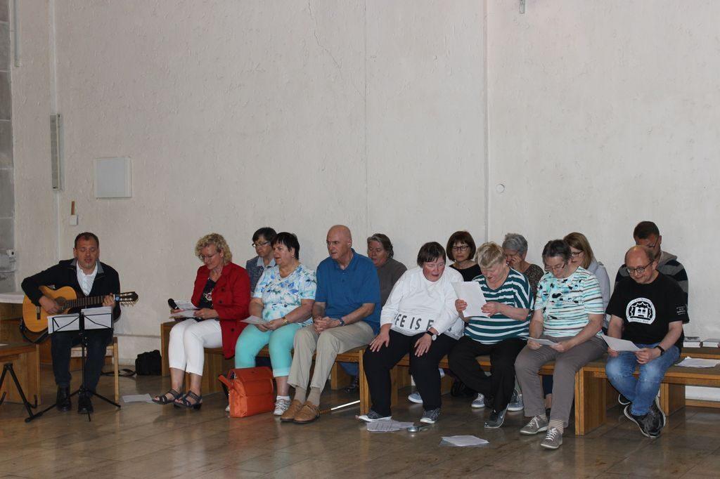 Bei der gemeinsamen Andacht: Ganz links sitzt Christian und spielt Gitarre. Neben ihm sitzen viele Teamkollegen aus dem Wundenetz und Menschen, die am Gottesdienst teilgenommen haben und singen.
