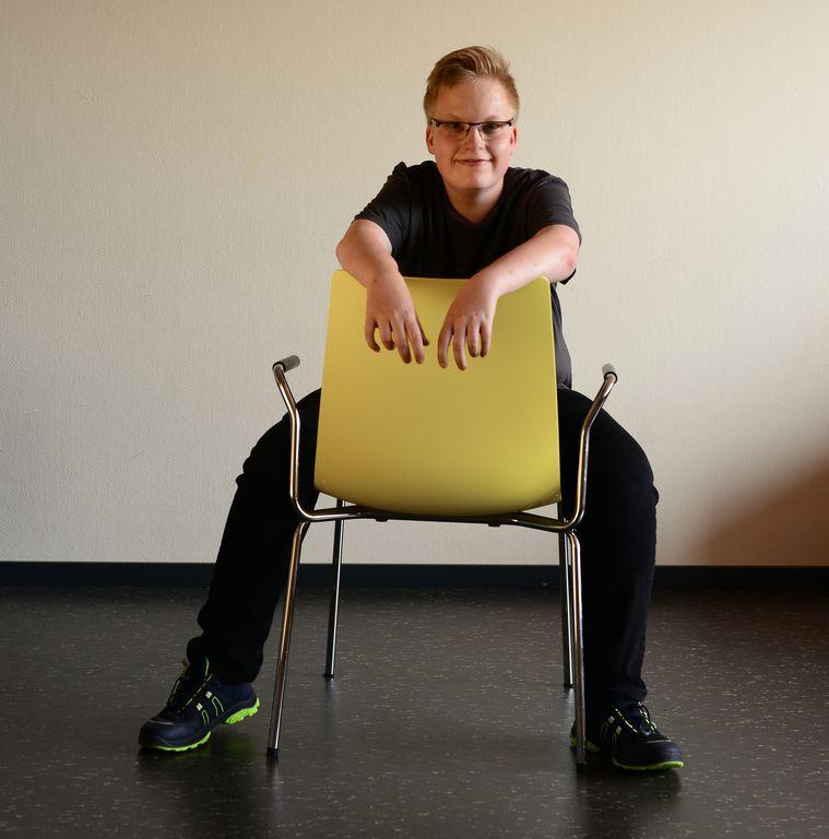 Julian in sehr cooler Pose falsch herum auf einem leiuchtend gelben Stuhl