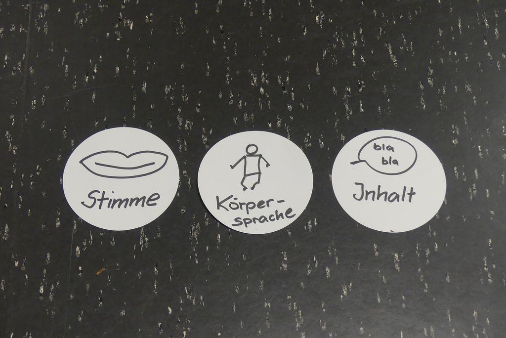 Auf dem Boden liegen drei runde Kärtchen. Darauf steht: Stimme, Körperhaltung und Inhalt.