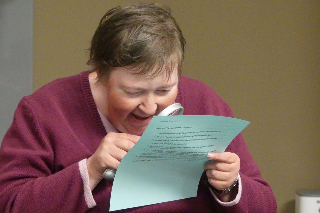 Silvia liest die Zungenbrecher mithilfe ihrer Leselupe.