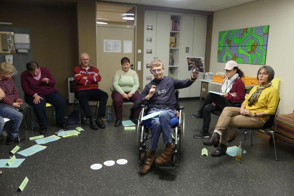 Werner sitzt im Rollstuhl in der Mitte des Kreises und hält einen Spontanvortrag.