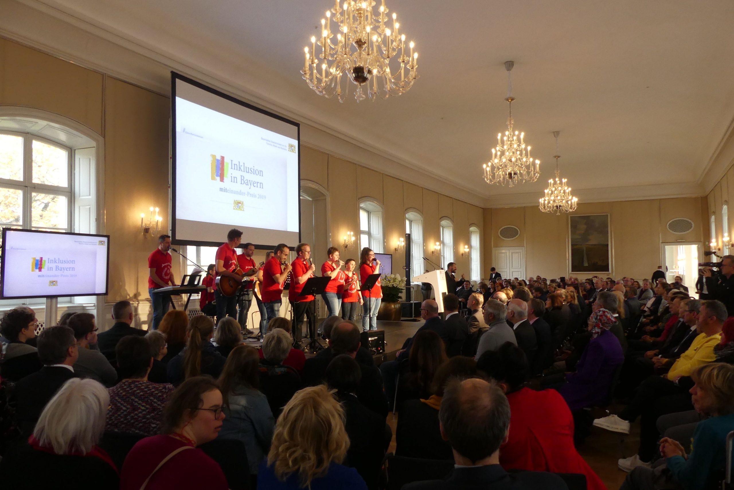 Im vollen Festsaal stehen die Mitglieder von Jura goes Music auf der Bühne bei ihrem Auftritt. Der Saal wird von festlichen Kronleuchtern erhellt.