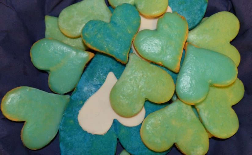 Auf dem Foto sind Plätzchen in Herzform zu sehen. Sie sind mit Zuckerguss in weiß, grün und blau verziert.