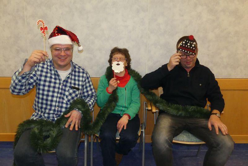 Auf dem Foto sind Daniel, Evi und Christoph zu sehen. Sie sitzen nebeneinander. Daniel trägt eine Glitzermütze und hält eine Zuckerstange hoch, Evi lächelt verschmitzt hinter einem weißen Nikolausbart hervor und Christoph schmückt sich mit einer coolen Pudelmütze.