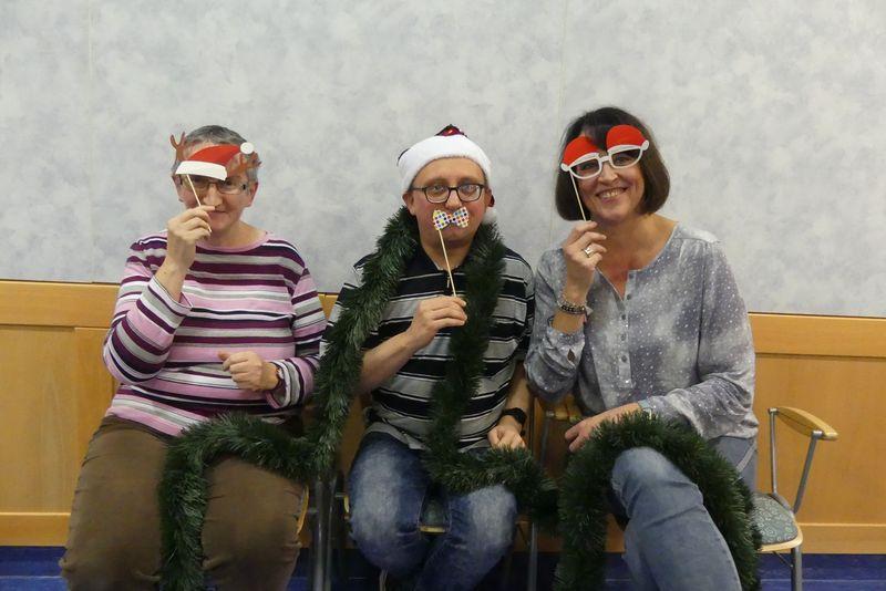 Auf dem Foto sitzen Birgit links und Sabine rechts neben Roland. Alle drei haben sich weihnachtlich geschmückt mit Nikolausmützen, Nikolausbrille und einer schicken Schleife.