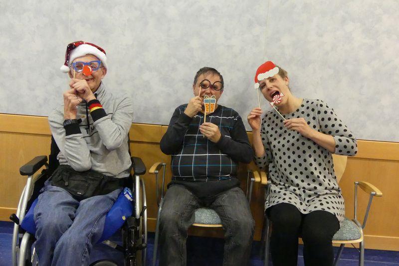 Auf dem Foto sitzt Werner mit Glitzermütze und roter Nase links. In der Mitte hat sich Martin mit Weihnachtsbrille und Geschenk verkleidet. Judith sitzt rechts, hat eine rote Weihnachtsmütze und will gerade von einem rotweißen Bonbon abbeißen.