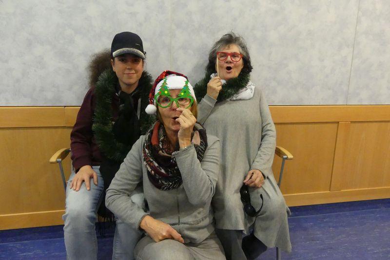 """Auf dem Foto ist Hildegard in der Mitte und sagt gerade """"Hohoho"""". Hinter ihr sitzen Janine und Anneliese. Alle drei haben sich mit weihnachtlichen Accessoires geschmückt: Janine trägt eine Tannen-Boa, Anneliese eine Weihnachtsbrille und Hildegard eine Glitzermütze und Christbaumbrille."""