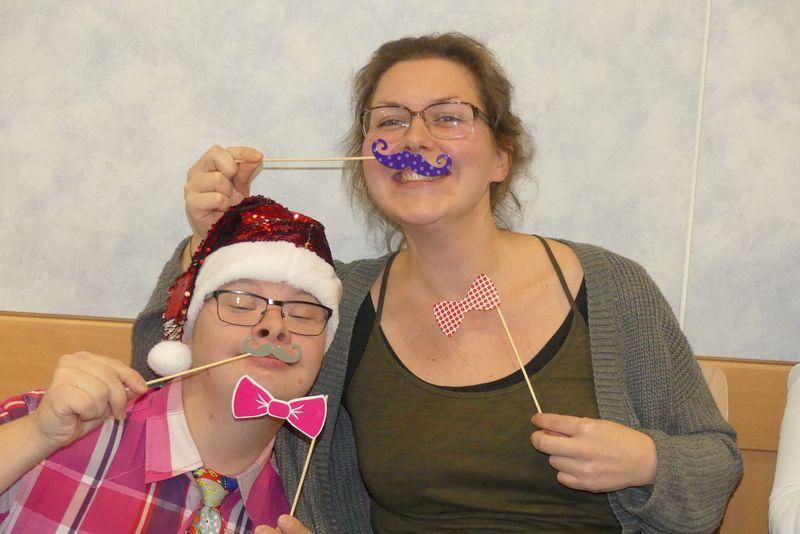 Auf dem Foto ist Torsten mit einer Glitzer-Nikolausmütze und einer roten Schleife. Janett hat sich mit einer weiß-rot-karierten Schleife und einem lilafarbenen Schnurrbart weihnachtlich geschmückt.