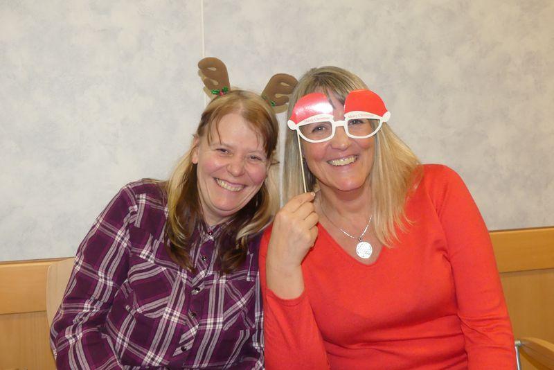 Auf dem Foto strahlen Michaela (links) und Geli (rechts) in die Kamera. Michaela trägt einen Haarreif mit Rentiergeweih und Geli eine Brille mit Nikolausmützen, die perfekt zu ihrem roten Pulli passt.