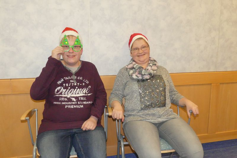 Auf dem Foto tragen Julian und Silvia Nikolausmützen und Julian blickt durch eine Tannenbaumbrille.