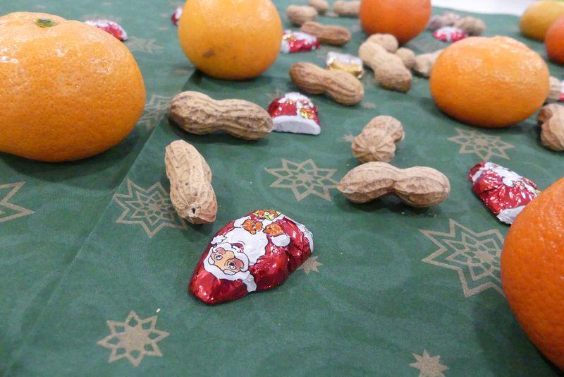 Auf einem grünen Tischtuch mit goldenen Weihnachtssymbolen liegen Mandarinen, ERdnüsse und kleine Schoko-Nikoläuse.