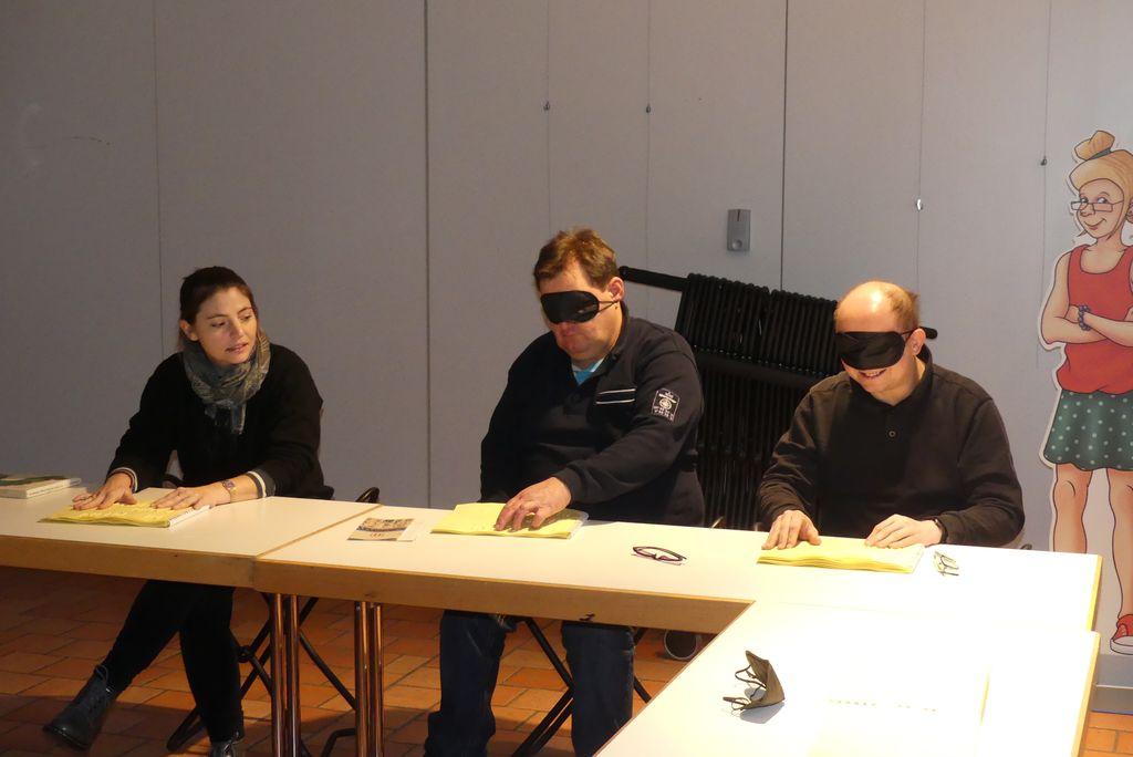 """Eine Museumsmitarbeiterin hilft uns, das Buch """"Die Raupe Nimmersatt"""" blind zu lesen: Robert und Roland tragen Augenmasken und befühlen das Tastbuch."""