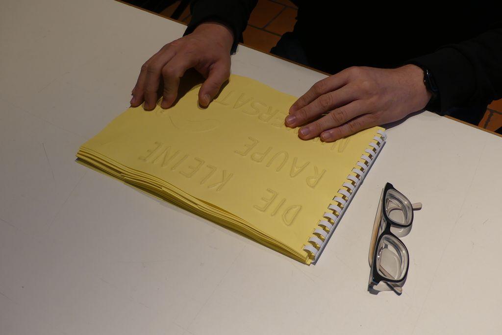 """Das Kinderbuch """"Die kleine Raupe Nimmersatt"""" kann man in der Ausstellung ganz neu kennen lernen: es ist ein Buch zum Fühlen, die Geschichte wird in Formen erzählt, die man ertasten kann. Auf dem Bild siehr man das Buch und Hände. Eine brille liegt daneben, sie wird gerade nicht gebraucht."""