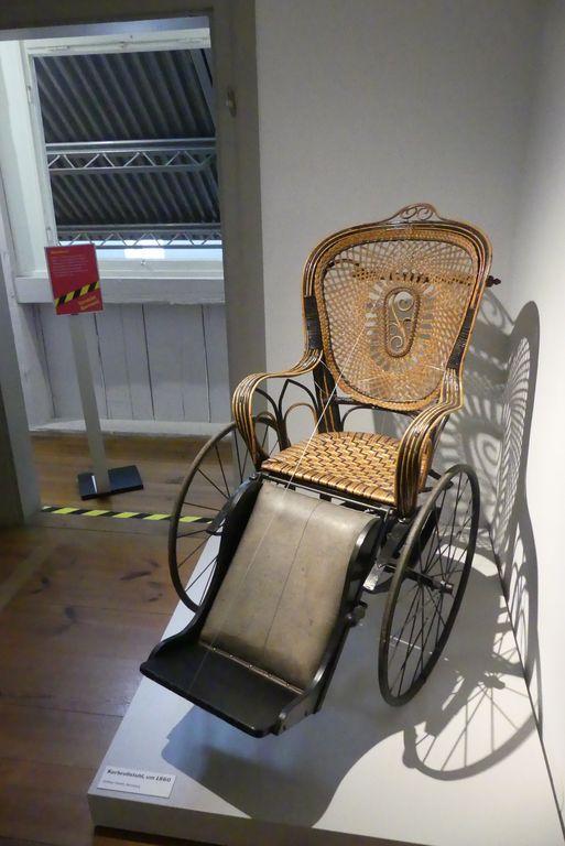 Ein sehr schöner Rollstuhl aus Holz und Rattan, der über 100 jahre alt ist, in der Austtellung.