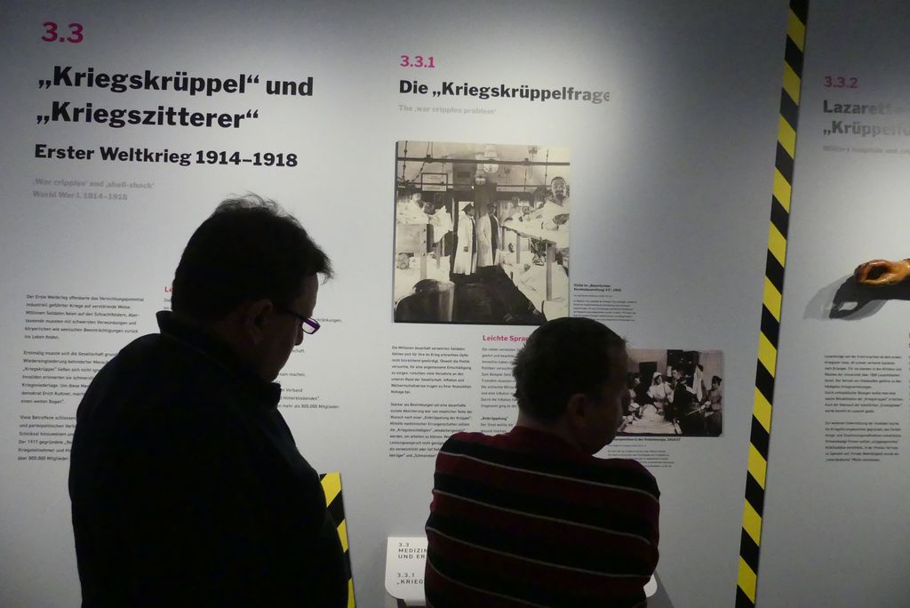 """Robert und Roland stehen vor Texttafeln, die über """"Kriegszitterer"""" aus dem Ersten Weltkrieg berichtet."""