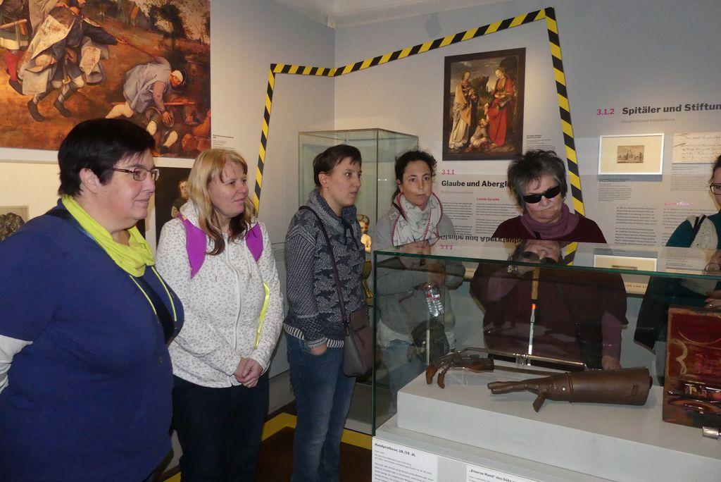 Karin, Michaela, Maria, Janine und Anneliese hören bei der Führung zu. Im Schaukasten vor ihnen liegen eine künstliche Hand aus Eisen und andere medizinische Gegenstände aus vergangenen Jahrhunderten.
