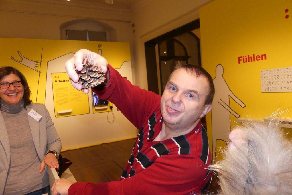 Martin hat in einer Fühlbox einen Kiefernzapfen ertastet. Im Hintergrund freut sich eine nette Museumsmitarbeiterin über unsere Begeisterung in der Mitmach-Abteilung.