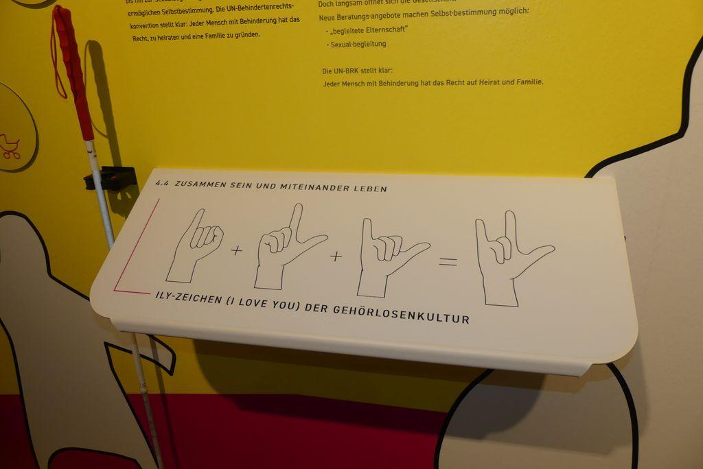 """Auf einer Tafel im Museum sieht man die Handzeichen I, L und Y, damit sagen gehörlose Menschen """"I love you""""."""