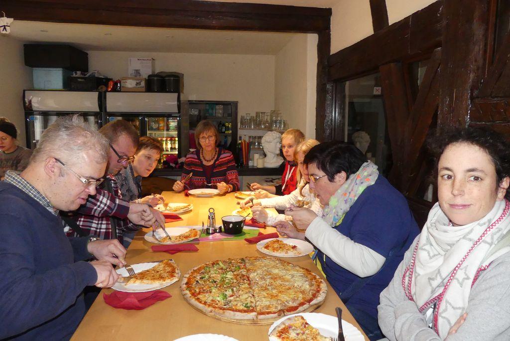 Wir genießen leckere Pizza. Man siehr einen langen Holztisch mit riesigen Pizzen und glücklich essende Teamkollegen.
