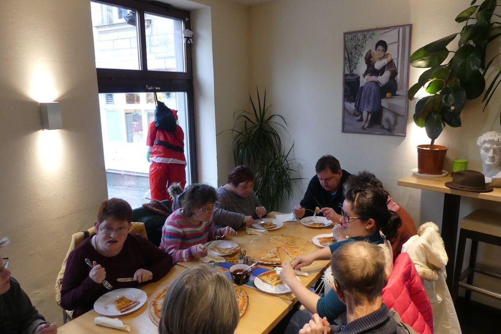 Zu unserem Besuch in Erlangen gehörte natürlich auch ein gutes Essen: Hier sitzt ein Teil unserer Gruppe an einem langen Tisch und genießt Pizza.
