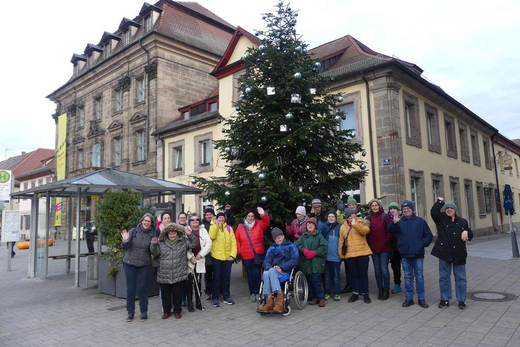 Auf dem Foto sind 20 unserer Mitglieder im Wundernetz zu sehen. Sie stehen vor einem großen Tannenbaum, der mit Lichterketten und hellblauen Kugeln geschmückt ist. Das Foto entstand bei unserem Weihnachtsausflug nach Erlangen ins Stadtmuseum und auf den Adventsmarkt.
