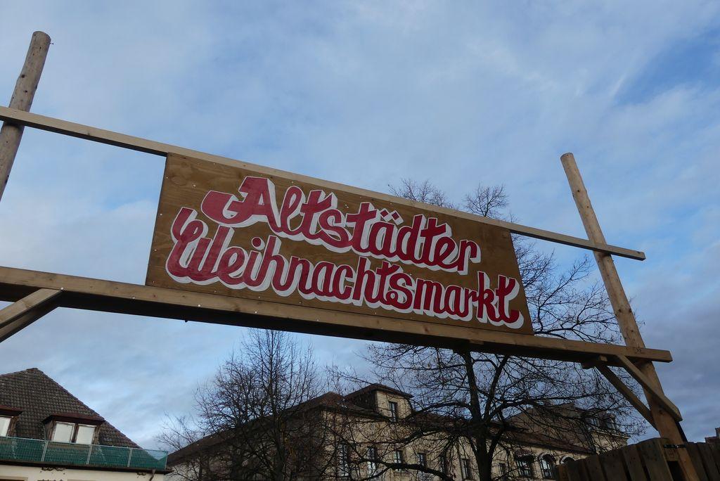 Auf einem Holzschild steht: Altstädter Weihnachtsmarkt.