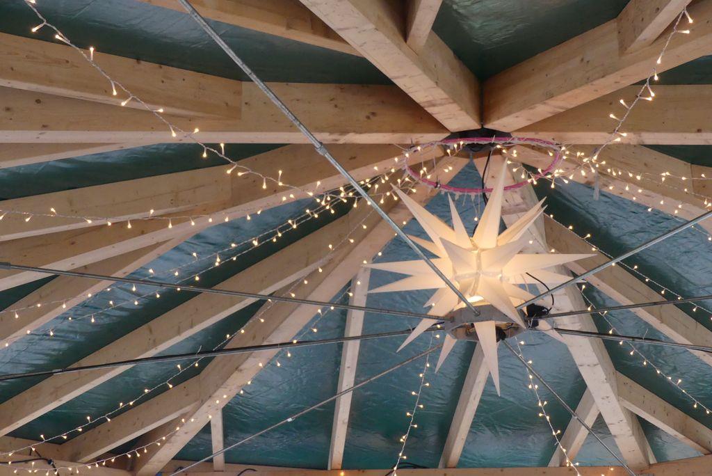 Ein sternförmiges Dach überspannt einen Pavillon- Lichterkette bilden einen Stern und ein leuchtender Papierstern ist in der Mitte.