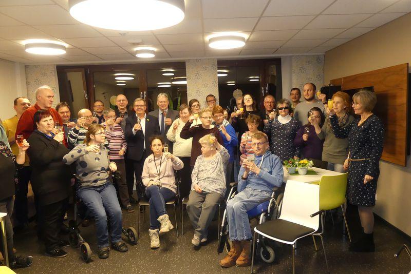 Gruppenbild mit Preisträgern und Gratulierenden und erhobenen Sektgläsern.