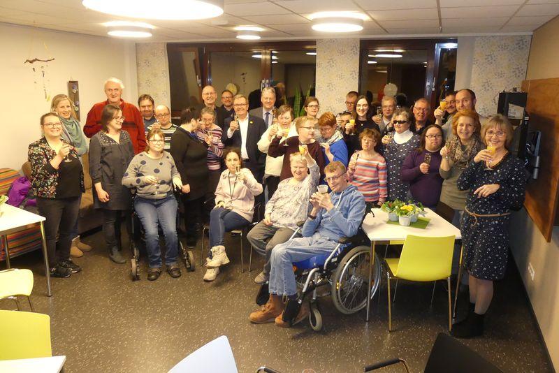 Gruppenbild mit Preisträgern und Gratulierenden sowie erhobenen Sektgläsern.