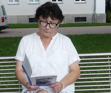 Auf dem Foto sitzt Anja im Grünen und schmökert in dem Buch.