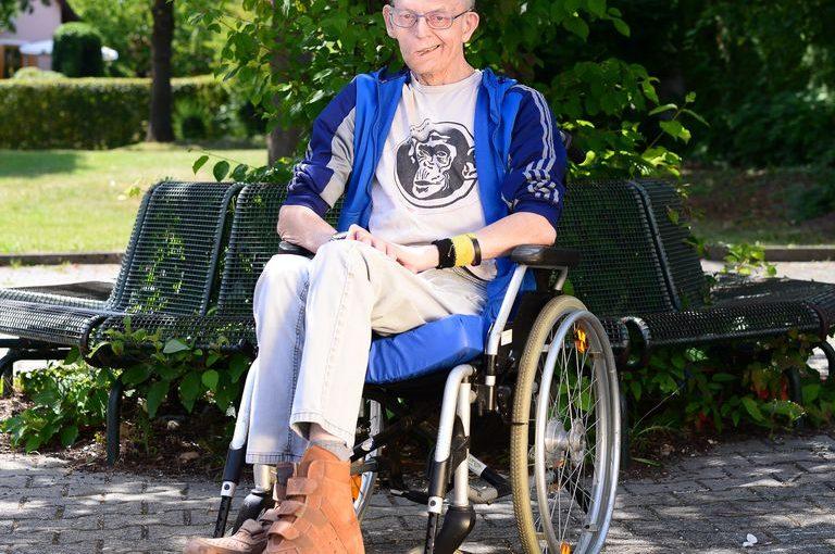 Werner sitzt im Rollstuhl im Grünen und lächelt in die Kamera.