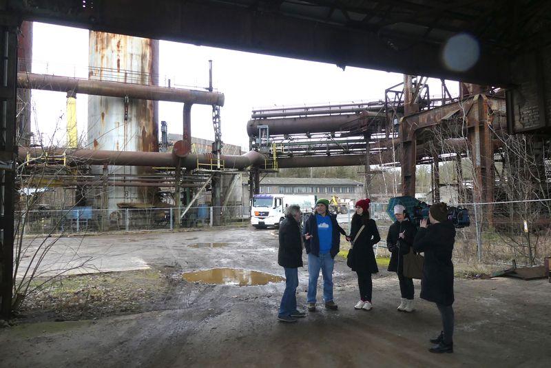 Dreharbeiten im alten Stahlwerk Maxhütte_ Herr Reyzl führt unser Team. Gerade stellen sich alle in der alten Gierßhalle unter. Mit dabei sind als Reporter Markus und Janine, OTV-Readakteurin Antonia und Kamerafrau Corinna.