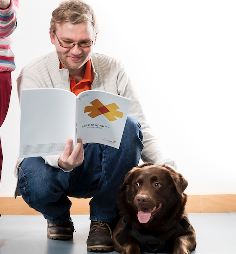 Andreas kniet und liest in einer Broschüre. Neben ihm liegt sein Hund Janosch.