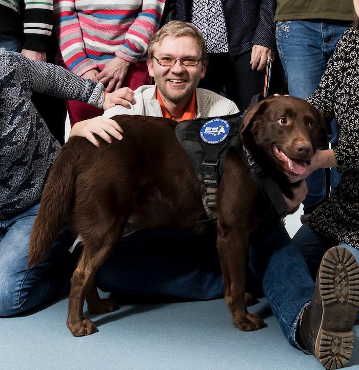 Andreas sitzt auf dem Boden und lächelt über den Rücken seines Hundes Janosch in die Kamera.