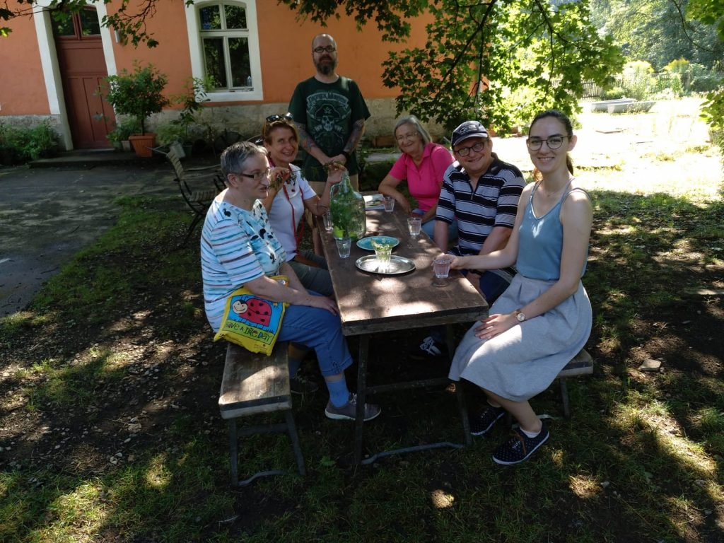 Unser Drehteam sitzt gemeinsam mit Frau Bräutigam an einem Holztisch im Grünen.