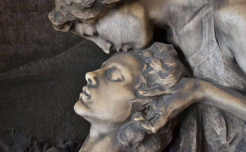 Foto von den Köpfen von zwei Statuen. Eine Frau liegt mit geschlossenen Augen entspannt da. Eine zweite Figur beugt sich von oben herab und küsst sanft die Stirn der Frau.