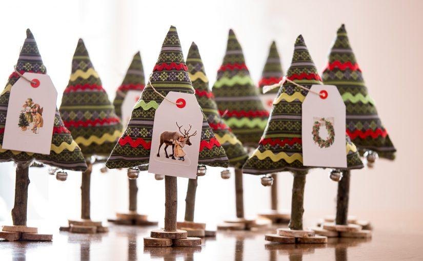 Viele bunte Christbaume aus Stoff mit Verzierungen auf einem kleinen Astständer. An den Bäumen hängen kleine Geschenkkärtchen.