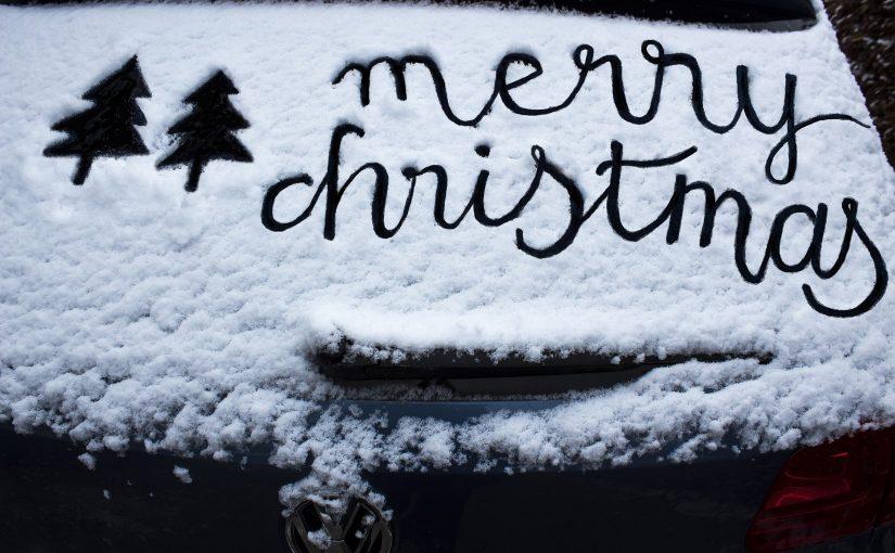 """Ein verschneites Autofenster. In den Schnee ist ein Tannenbaum gezeichnet und es steht da: """"Merry Christmas"""""""