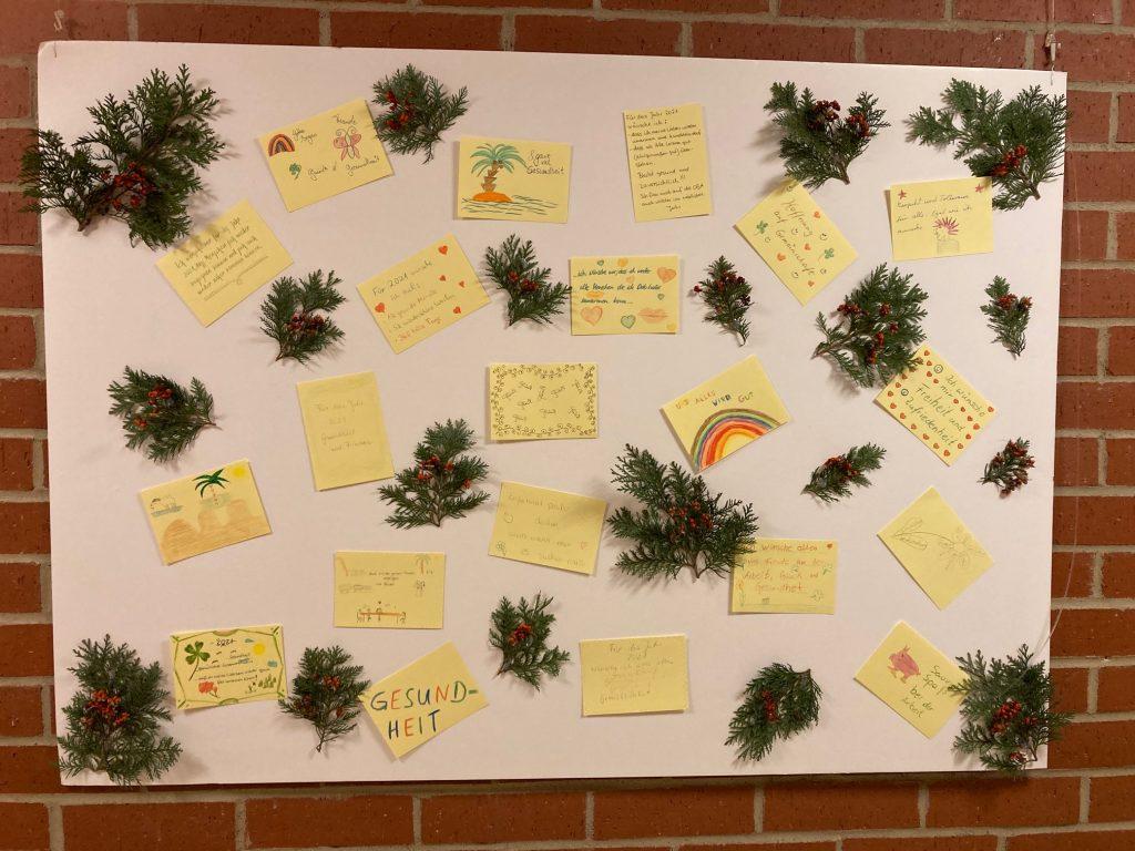 Auf dem Bild ist eine Pinnwand. Darauf sind kleine Weihnachtszweige festgemacht und viele gelbe Zettel. Auf den Zetteln sind gezeichnete oder aufgeschriebene Neujahrswünsche.